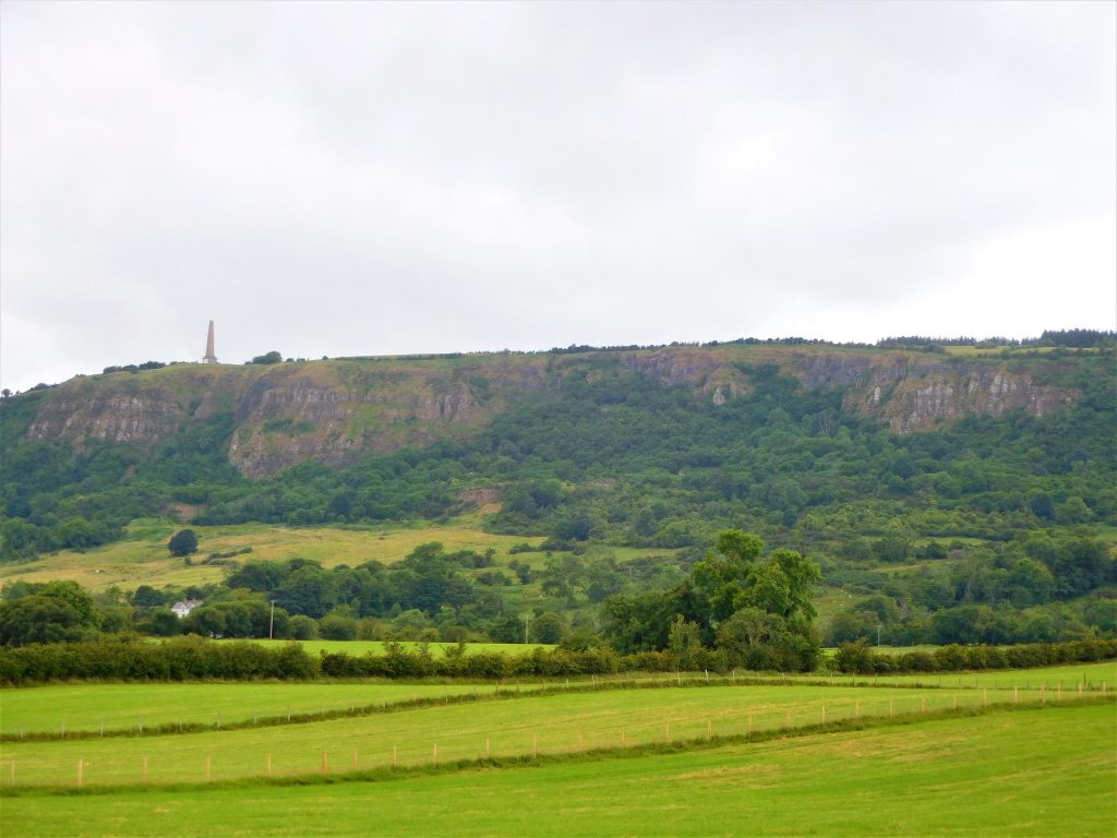 Knockagh Monument and surrounding cliffs where O'Haughan's Cave is located